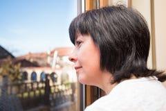 Brunetki kobieta przyglądająca out okno Zdjęcia Royalty Free
