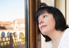 Brunetki kobieta przyglądająca out okno Zdjęcia Stock