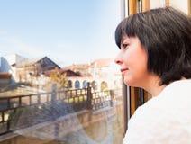 Brunetki kobieta przyglądająca out okno Obrazy Royalty Free