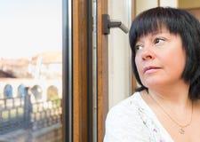 Brunetki kobieta przyglądająca out okno Zdjęcie Royalty Free