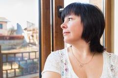 Brunetki kobieta przyglądająca out okno Fotografia Royalty Free