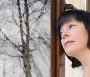Brunetki kobieta przyglądająca out okno Obraz Royalty Free