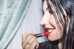 Brunetki kobieta stosuje czerwoną pomadkę jej wargi Fotografia Stock