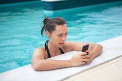 Brunetki kobieta texting od pływackiego basenu zdjęcia royalty free