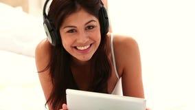 Brunetki kobieta używa pastylka komputer osobistego podczas gdy słuchający muzyka zbiory