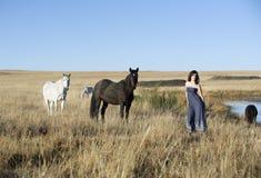 Brunetki kobieta w śródpolnej pozyci obok koni obrazy stock
