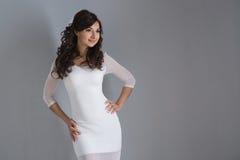 Brunetki kobieta w biel sukni na szarym tle fotografia stock