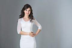 Brunetki kobieta w biel sukni na szarym tle zdjęcia royalty free