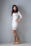 Brunetki kobieta w biel sukni na szarym tle zdjęcie royalty free