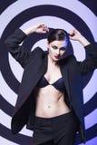 brunetki kobieta w biznesowym kostiumowym oświetleniu papieros przed lustrem z koloru backlight Zdjęcie Royalty Free