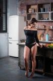 Brunetki kobieta w czarnym bikini pozuje w kuchni Zdjęcie Royalty Free