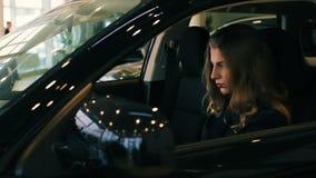 Brunetki kobieta w Luksusowych Samochodowych salonu mienia rękach na kierownicie zbiory