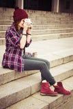 Brunetki kobieta w modnisia stroju obsiadaniu na krokach i fotografować na retro kamerze na ulicie obraz tonujący Fotografia Stock