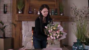 Brunetki kobieta w przypadkowym kwiecistym artyście, kwiaciarnia opakunki kwitnie - różowe róże w prezenta papierze przy warsztat zbiory