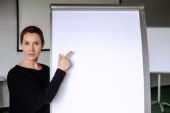 Brunetki kobieta wskazuje przy flipchart w biurze zdjęcie stock