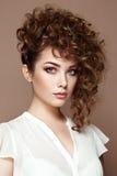 Brunetki kobieta z kędzierzawym i błyszczącym włosy obrazy stock