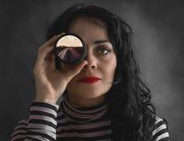 Brunetki kobieta z kamera obiektywem w jej oku z fotografią, obrazy stock