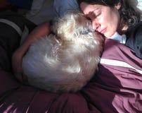 Brunetki kobiety dosypiania zachodniego średniogórza białego teriera cuddling pies Fotografia Stock