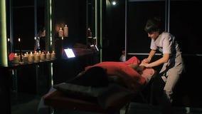 Brunetki kobiety lying on the beach na masażu stole w piękno salonie, podczas gdy fachowy terapeuta znosi masaż zbiory
