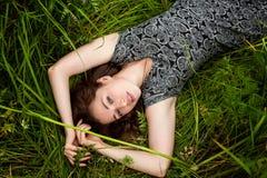 Brunetki kobiety lying on the beach na zielonej trawie obrazy royalty free