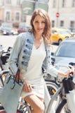 Brunetki kobiety obsiadanie na rowerowym pobliskim roweru parking Obraz Stock
