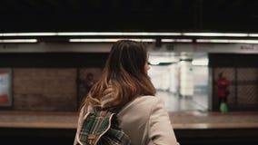 Brunetki kobiety pozycja na staci kolejowej i czekaniu dla jej pociągu Dziewczyna w metrze przy wieczór spojrzeniami na szybkich  Obraz Stock