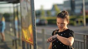 Brunetki kobiety pozycja przed mapą przy miastem, dziewczyna przyglądającym autobusowym rozkładem i patrzeć zegarek, zdjęcie wideo