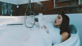 Brunetki młoda dziewczyna bierze kąpielowy pełnego piana w łazience wanna Podwyżki noga zdjęcie wideo