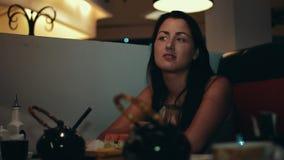 Brunetki młoda dziewczyna przy stołem w suszi restauraci dinner Rozmowa z someone zbiory