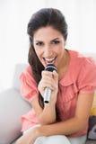 Brunetki obsiadanie na jej kanapa śpiewie w mikrofon patrzeje Fotografia Royalty Free