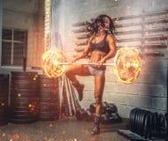 Brunetki sprawności fizycznej kobieta ćwiczy z płonącym barbell fotografia royalty free