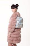 Brunetki uśmiechnięta nastoletnia dziewczyna w różowym futerkowym żakiecie reklamuje plecaka, obrazy stock