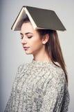Brunett för flickastudent i en varm tröja som läser en bok och drömma fotografering för bildbyråer