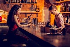 Brunett i den röda klänningen som väntar på hennes drink i stången fotografering för bildbyråer