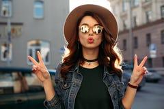 Brunett i hatten som visar fred och överför kyssen arkivfoto