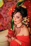 Brunett i rött med idérikt smink Royaltyfri Bild