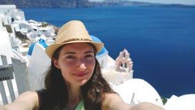 Brunett i sugrörhatten som tar en selfie på bakgrunden av Oia på den Santorini ön fotografering för bildbyråer