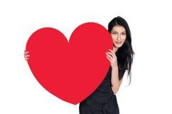Brunett i svart klänning med hjärta som göras av papper arkivfoto