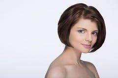 Brunett med kort hår som ser kameran på isolerad vit Arkivbild