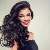 Brunett med länge, tätt lockigt hår fotografering för bildbyråer