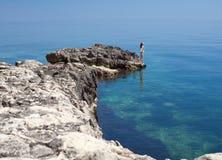 Brunett på rock på havet royaltyfri fotografi