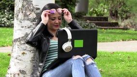 Brunett p? gr?set med en dator stock video