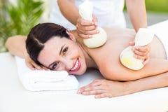 Brunett som har massage med växt- kompressar Royaltyfria Foton