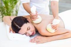 Brunett som har massage med växt- kompressar Arkivbild