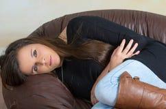 Brunett som krullas upp i soffa Royaltyfri Foto