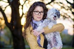 Brunett som ler kvinnan som kramar hennes utomhus- vita hund arkivbild