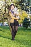 Brunett som ler kvinnan som kramar hennes utomhus- vita hund royaltyfria bilder