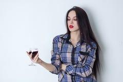 Brunett som rymmer ett exponeringsglas av vin och ser det Arkivfoto