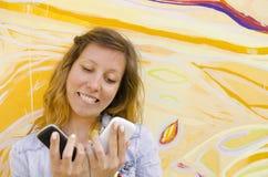 Brunett som ser två mobiltelefoner arkivfoton