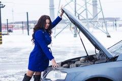 Brunett som ser under huven av hennes bil Royaltyfria Bilder
